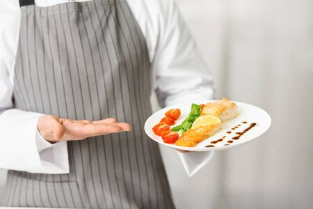Unrecognizable Chef Holding Plate With Cooked Salmon Steak Serving Fish Dish In Restaurant Kitchen. Cropped, Selective Focus Stock Photo