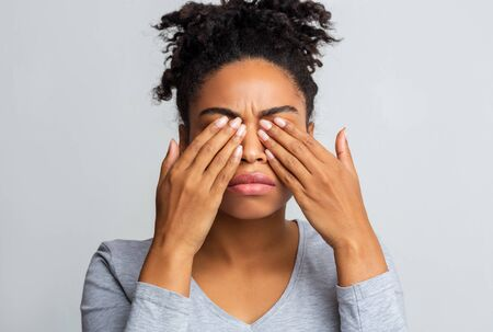 African girl rubs her eyes, suffering from conjunctivitis, ocular diseases concept Stock Photo