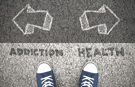 Recovery Concept, Addiction Or Health Written On The Asphalt Road. Above view of feet on the ground