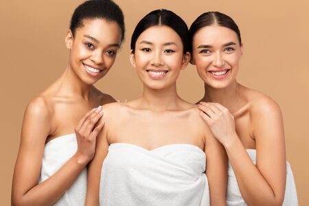 Beauty And Skin Care. Three Diverse Women In Bath Towels Smiling At Camera Posing Over Beige Background. Studio Shot Stock fotó