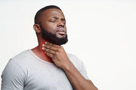 Trauriger schwarzer Kerl, der unter Halsschmerzen leidet, den hervorgehobenen Hals berührt, Platz kopiert Standard-Bild