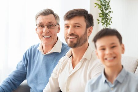 Multi-Generational Family. Joyful Senior Man, His Adult Son And Grandson Boy Smiling At Camera Sitting On Sofa At Home.