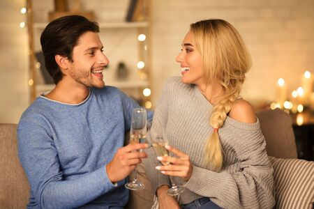 True love. Beautiful couple drinking champagne and looking at each other in cozy living room Stock Photo - 136942269