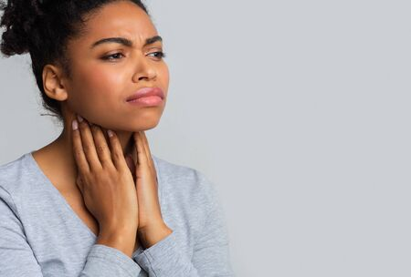 Sad black woman suffering from pain in throat, touching her neck, empty space
