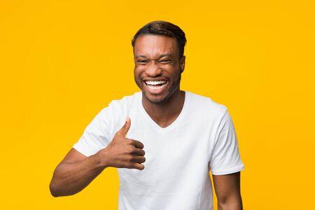 Mögen. Positiver schwarzer Mann lacht und gestikuliert Daumen hoch und genehmigt lustigen Witz, der über gelbem Hintergrund steht. Studioaufnahme