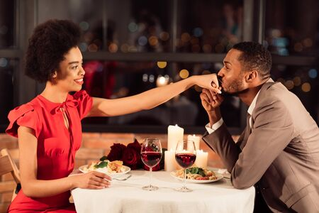 Romantic Date. Black Man Kissing Womans Hand Dining In Restaurant. Couple Of Lovers Celebrating Valentines Day. Stock Photo - 136942431