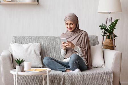 Sorridente ragazza musulmana in velo utilizzando smartphone a casa, messaggistica o navigazione sui social network, relax sul divano in soggiorno, spazio copia