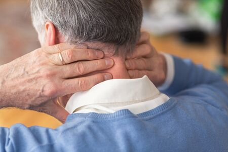 Unrecognizable Elderly Man Having Neck Pain Suffering From Arthritis Massaging Aching Nape Sitting On Sofa Indoor. Rear View, Selective Focus Stock Photo