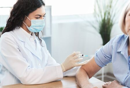 Seasonal Flu Shot. Mexican doctor in medical mask injecting tetanus toxoid vaccine to mature woman, copy space