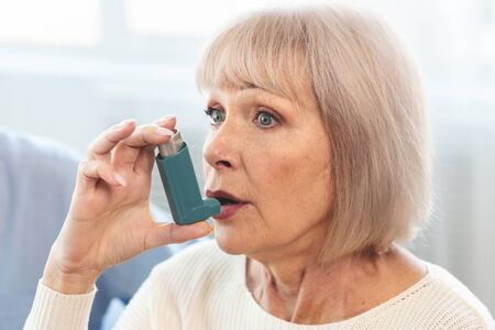 Senior Woman Using Asthma Inhaler For Allergies In Modern Clinic, Copy Space