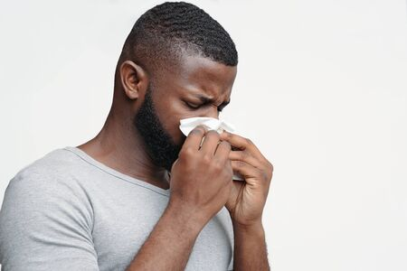 Afro man touching his nose with napkin, having runny nose, got flue, free space
