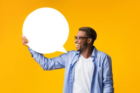 Opinion. Happy Afro Guy Holding Blank White Speech Bubble Showing What He Thinks Standing Over Yellow Studio Background. Mockup