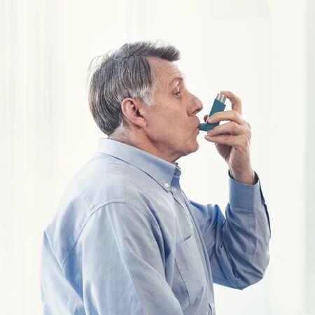 Asthma Attack. Side view of mature man using inhaler for allergies in modern clinic, copy space