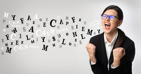 Problems at work concept. Portrait of angry businesswoman screaming, alphabet letters coming out of open mouth over light background 写真素材