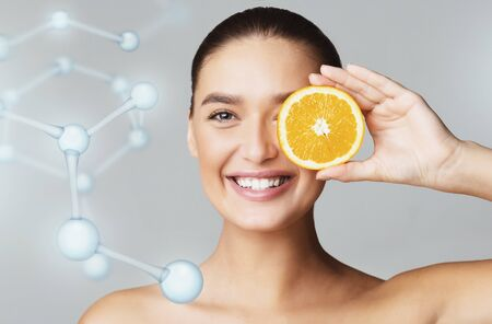 Happy young beautiful woman covering eye with orange half over grey background, molecular model, modern beauty industry concept