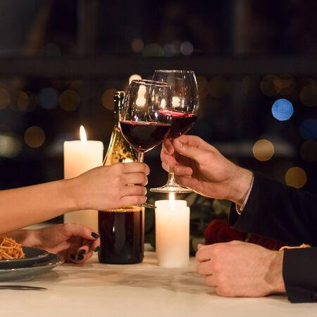 Hands of couple holding glasses of wine on restaurant on restaurant background. Happy Valentine celebration concept Stock Photo - 137078847