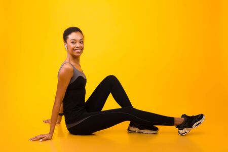 Sporty Girl In Earphones Sitting On Fitball Over Yellow Studio Background. Workout And Fitness. Empty Space Banque d'images - 137180591