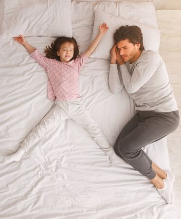 Dad and little girl sleeping together on bed, top view, fatherhood, parenthood, love concept
