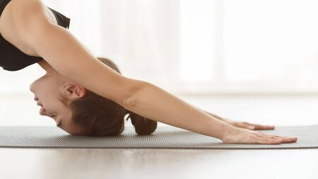 Yoga for mind. Girl laying face down on yoga mat, stretching and meditating, side view Imagens