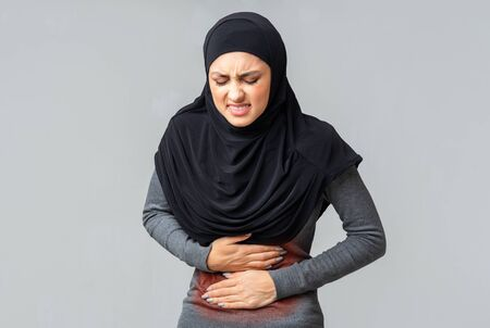 Menstrual cramps. Arabic woman in hijab suffering from acute abdominal pain with red sore spot on stomach, grey studio background with free space