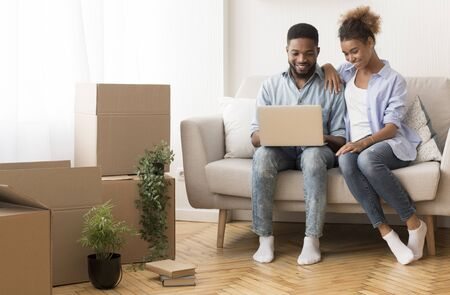 Joyful African American Couple Using Laptop Computer Sitting On Sofa Among Moving Boxes In New House. Free Space Banque d'images - 137181803