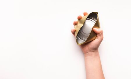 The concept of separate trash. Woman hand holds a crumpled tin can on a white isolated background, copy space