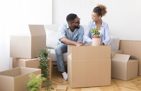 Happy Afro Spouses Preparing For Relocation Packing Moving Boxes Sitting On Couch Indoor. Selective Focus, Copy Space Banque d'images - 137184494