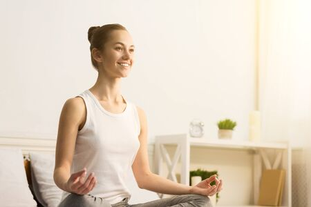 Happy woman doing anti-stress yoga in morning, meditating on bed, free space Banque d'images - 137184451