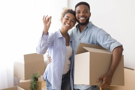 Joyful Afro Spouses Showing Key Embracing And Holding Moving Box After Relocation Standing In New Flat. Selective Focus