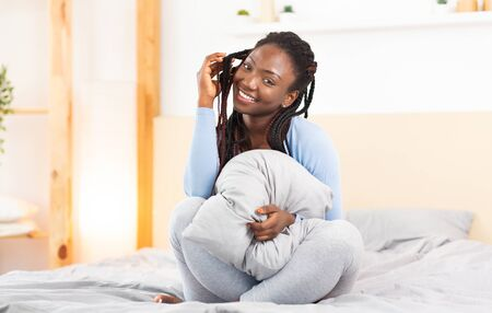 Smiling Black Lady Holding Blanket Playing With Braided Hair Sitting And Posing In Bed At Home In Morning. Selective Focus Banque d'images - 137184781