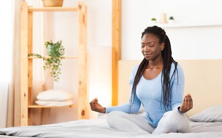 Meditation And Relaxation. Black Girl Doing Morning Yoga Sitting In Lotus Position Relaxing In Bed At Home. Free Space Banque d'images - 137184736
