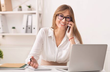 Business Call. Joyful Office Girl Talking On Cellphone Working At Laptop Sitting At Workdesk Indoor Banque d'images - 137184471