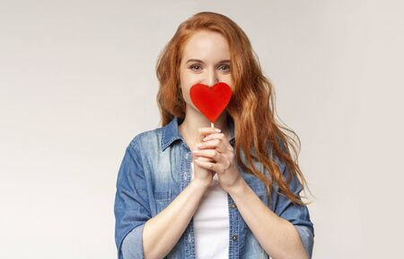 I fell in love. Excited redhead teen girl covering mouth with paper heart trying not to show her romantic feelings, copy space Banco de Imagens