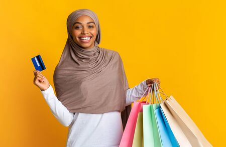 Cashback bonus concept. Happy black muslim girl in hijab holding credit card and colourful shopping bags over yellow background, free space