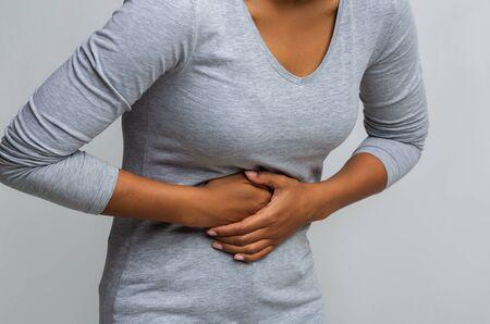 Bijgesneden van zwarte vrouw die lijdt aan gastritis en haar buik aanraakt Stockfoto