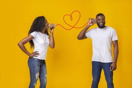 Atractiva chica negra enamorada hablando por teléfono con su novio, el amor está en el aire, fondo amarillo del estudio, espacio vacío Foto de archivo