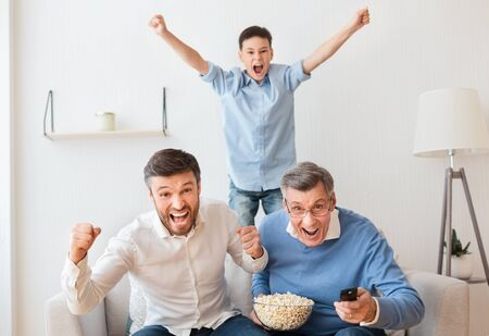 Male Family Of Grandfather, Father And Son Watching Sports On TV Celebrating Victory Sitting On Couch At Home Stock Photo - 137317746
