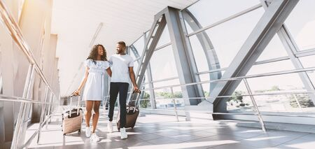 Ready for honeymoon. Wide shot of happy black couple walking with suitcases at airport terminal, low angle view, horizontal banner, panorama