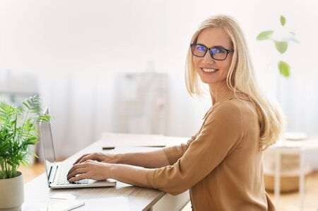 Successful businesswoman sitting at laptop and smiling to camera at workplace, free space Banque d'images - 137188849