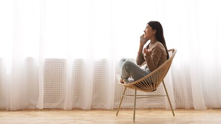 Happy girl talking on phone, sitting in modern armchair near window, panorama with copy space Banque d'images - 137186686
