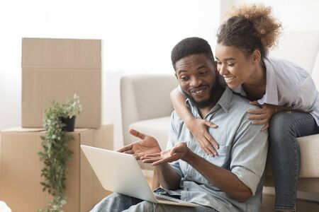 Moving House. Afro Man Using Laptop Showing Wife Relocation Services Sitting On Sofa Indoor. Empty Space Banque d'images - 137188855