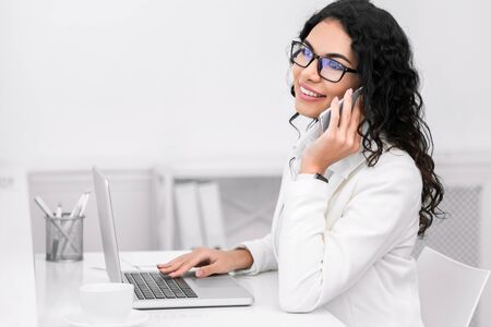 Work Call. Happy mexican manager talking on cell phone, sitting at desk using laptop. Free space Banque d'images - 137188692