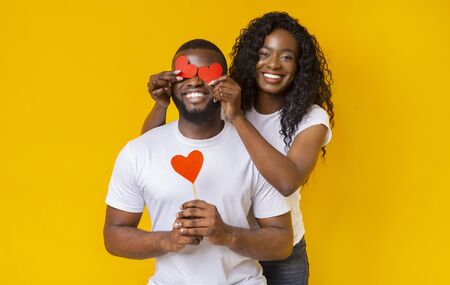 Smiling african american woman closing her man eyes with valentine cards, guy holding heart shaped red card, yellow background 스톡 콘텐츠