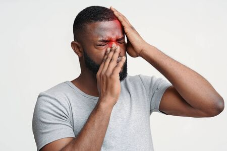 Sick black man having pain in forehead and nose, suffering from antritis
