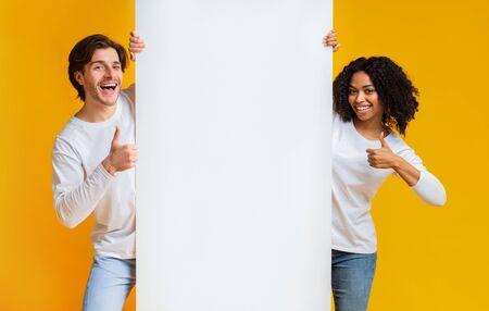 Happy Interracial Couple Holding White Advertising Board And Showing Thumbs Up, Recommending Something Over Yellow Studio Background, Free Space