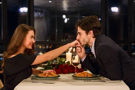Handsome man kissing hand of attractive woman in restaurant during romantic date Stock Photo - 137188863