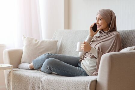 Weekend Leisure. Smiling Arabic Woman In Hijab Talking On Cellphone And Drinking Morning Coffee, Resting On Sofa At Home, Free Space Banque d'images - 137190746