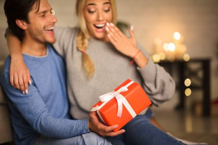 Happy valentine day! Man giving his girlfriend gift box, celebrating holiday at home Stock Photo - 137317818