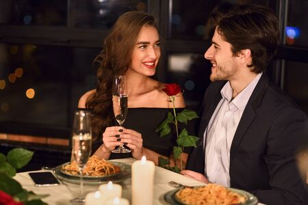 Couple in love having dinner in restaurant, woman drinking champagne, man holding rose smiling and talking Banque d'images - 137190618