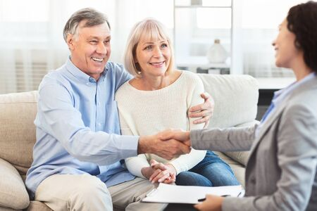 Real Deal. Real estate agent giving handshake to smiling elderly couple after successful agreement, free space Reklamní fotografie
